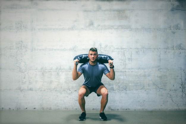 un sportif utilisant un bulgarian bag pour son entrainement fonctionnel de cross training