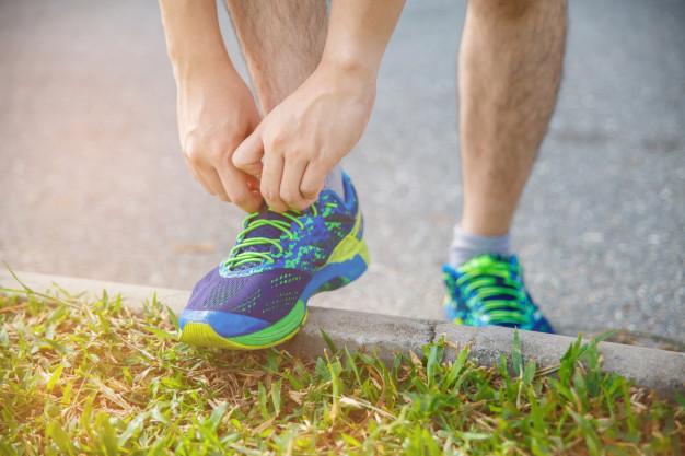 un homme en train de lacer ses chaussures de running