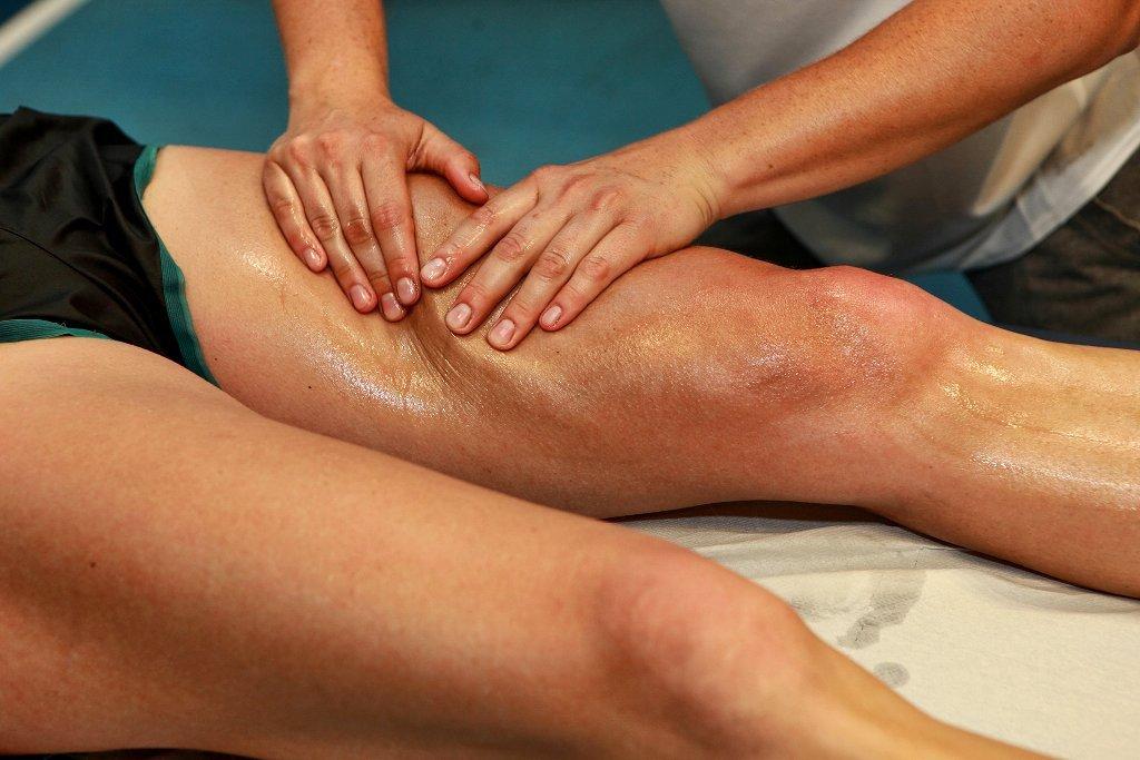 Un coach sportif réalisant un massage running pour son athlète