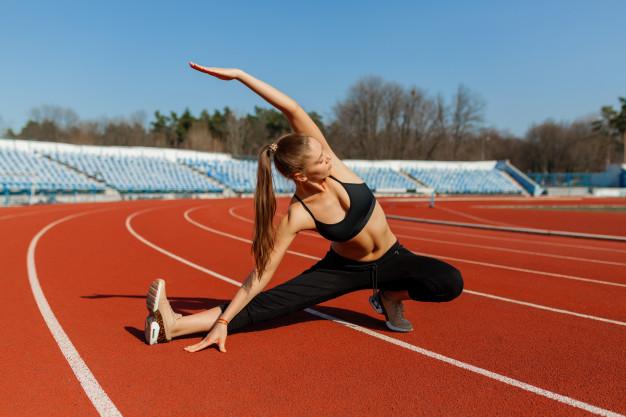Echauffement running d'une femme dans un stade