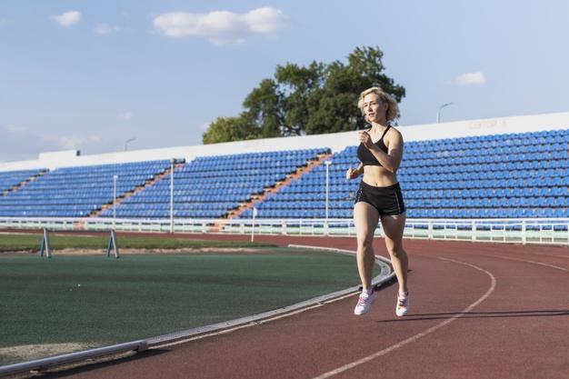 Une femme accélère progressivement sa course pour s'échauffer avant une séance de running dans un stade
