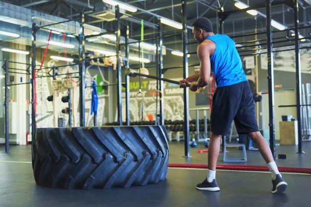 un sportif frappant sur un pneu : faire du cross training pour utiliser du matériel d'entrainement inédit
