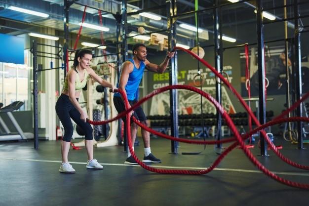 deux sportifs en train de faire du cross training dans une salle de sport