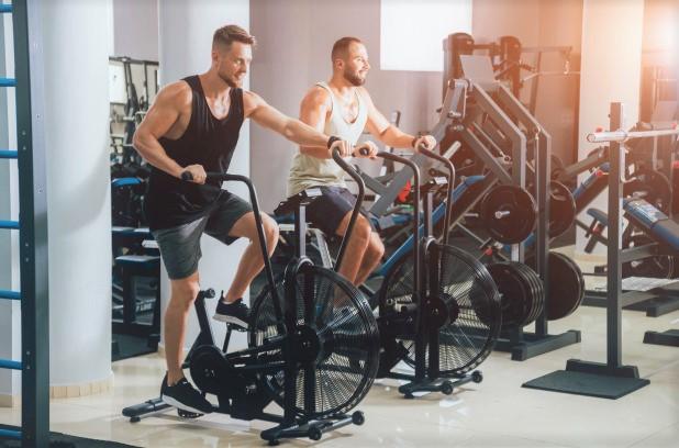 deux hommes en train de réaliser une séance de cross training avec un Air Bike