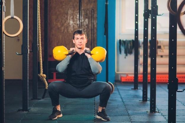 un homme réalisant un front squat avec kettlebell pendant une séance de cross training
