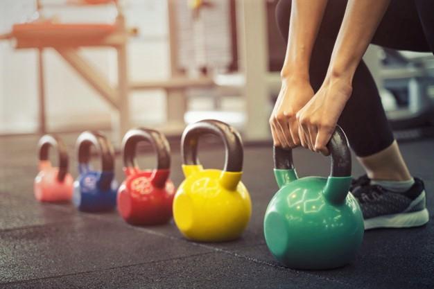 une femme entrain de s'entraîner avec des kettlebells de poids différents