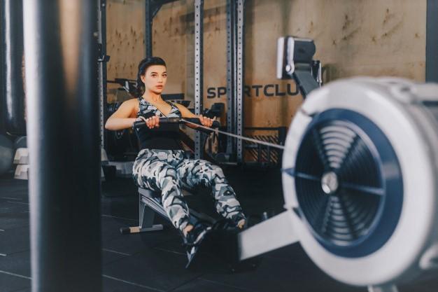 une femme renforçant son système cardio vasculaire avec un rameur : l'association de plusieurs disciplines aux origines du cross training