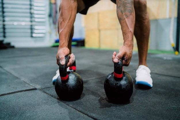 un homme s'entrainant avec des kettlebells afin de renforcer ses muscles