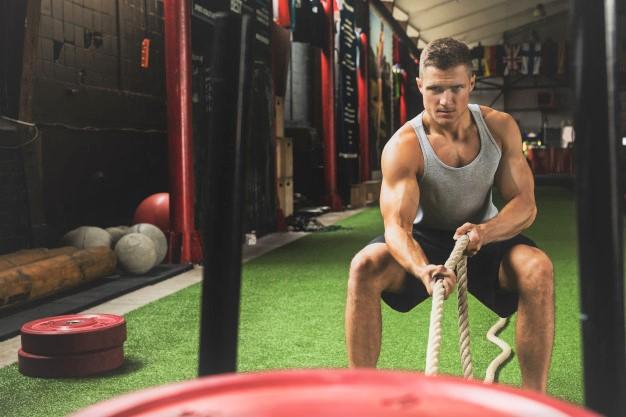 un sportif en train de tirer des charges avec une corde : un mouvement fonctionnel aux origines du cross training
