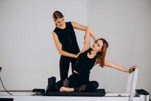 un coach et son élève font du pilates pour renforcer les muscles