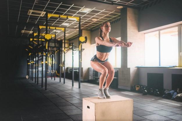 une femme muscle ses jambes avec un entrainement de cross training utilisant une jump box