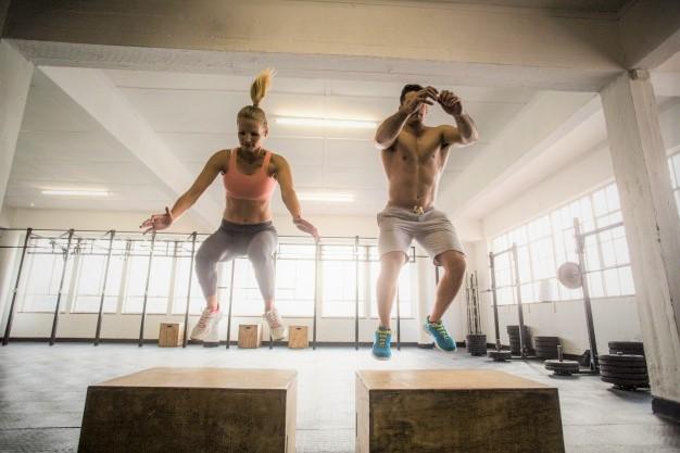 un couple de sportifs en train de sauter sur une plyo box
