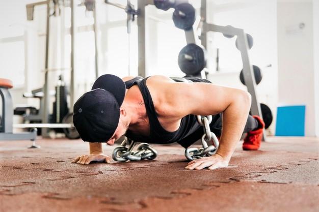 un homme réalisant des pompes lestées dans le cadre d'une séance de cross training