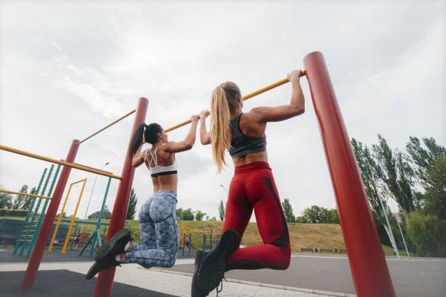 deux femmes s'entrainent en extérieur avec une barre de traction