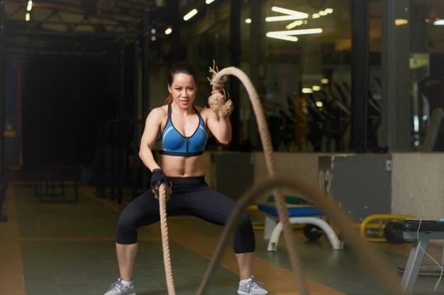 une jeune femme pratiquant le cross training en version scaled pour s'entrainer avec un corde ondulatoire