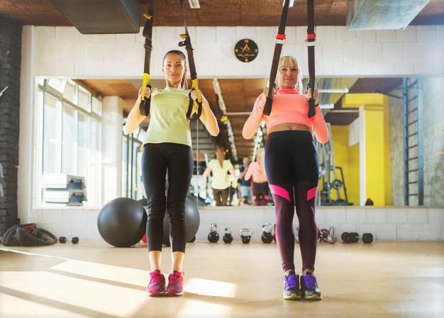 deus jeunes femmes en train de réaliser un entrainement en suspension, le training à l'origine du trx