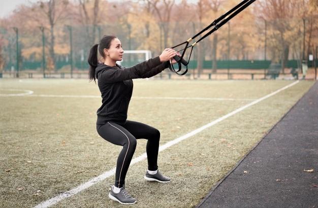 une femme réalisant un exercice avec trx dans un stade