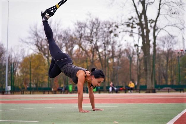 une femme utilisant un trx pour réaliser des exercices issus de la gymnastique