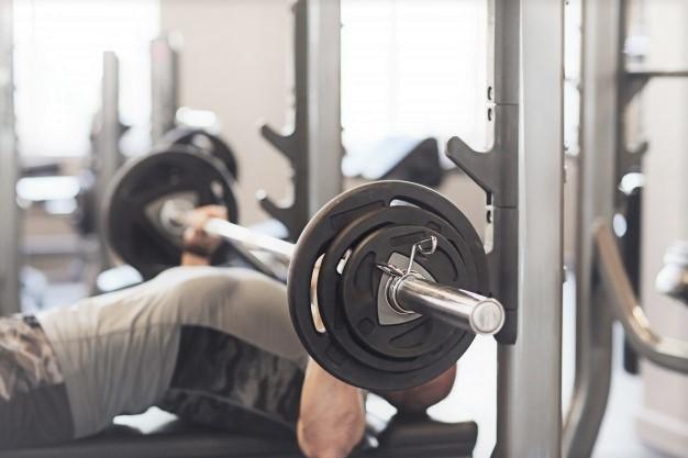 un homme réalisant l'exercice du développé couché avec l'aide d'un rack de musculation