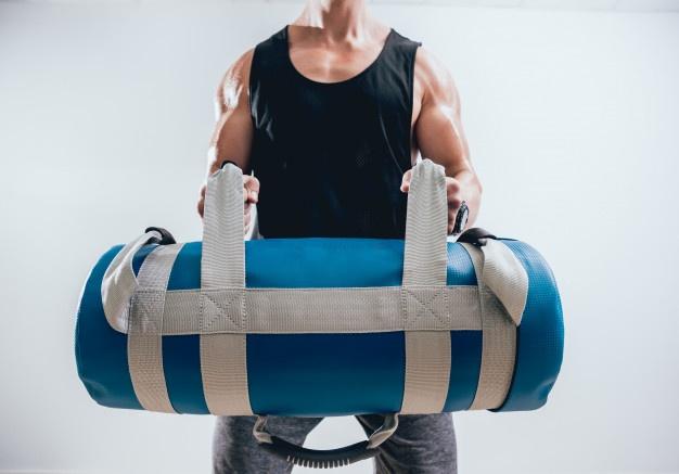 un homme utilisant un sandbag dans le cadre de sa préparation  physique