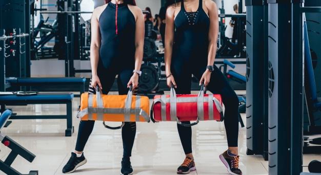 deux jeunes femmes utilisant un sandbag pour renforcer leurs muscles