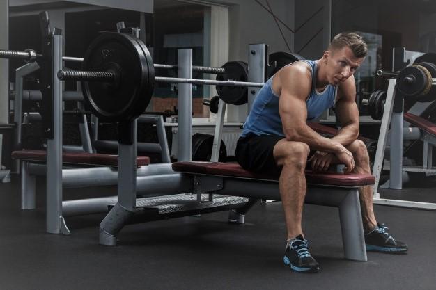 un sportif faisant du développé couché avec un banc de musculation dans une salle de remise en forme
