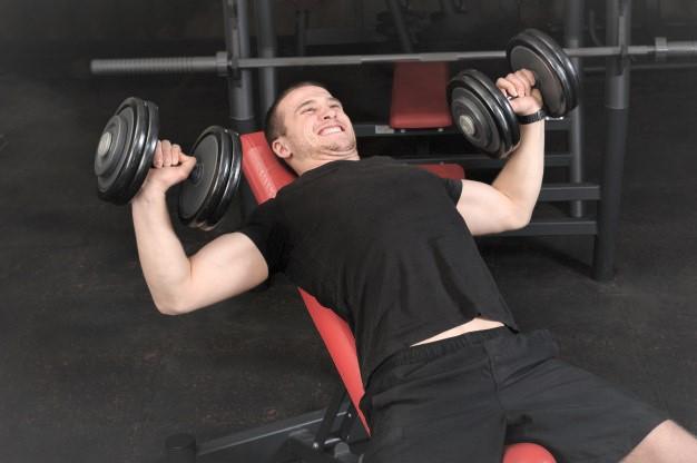 un homme faisant du développé haltères avec un banc de musculation incliné