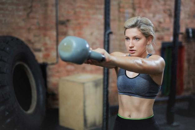 une femme réalisant un kettlebell swing en salle de cross training