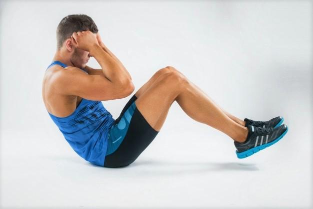 Un homme en pleine séance sportive réalise un sit up.