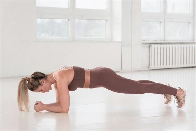 Une femme réalise un gainage grand droit, exercice adapté pour obtenir un ventre plat.