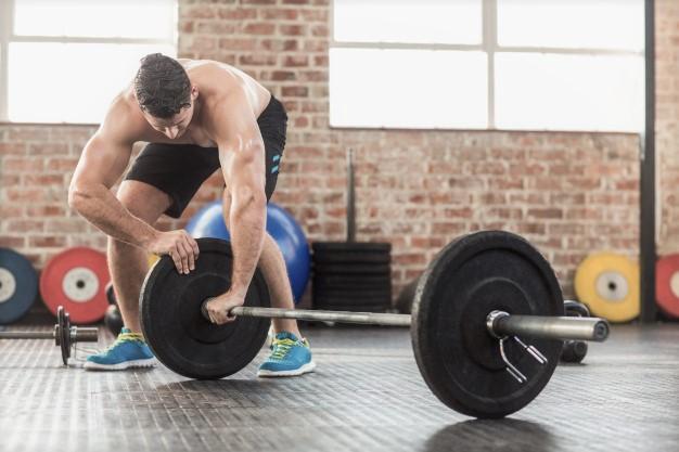 un sportif en train de décharger sa barre de musculation pour continuer son drop set