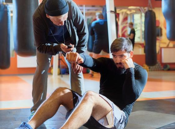 un homme en train de se préparer physiquement, accompagné par un coach sportif personnel
