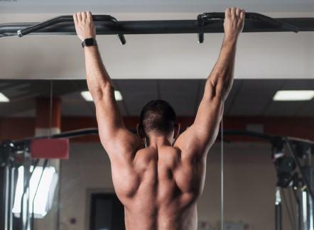 un homme suspendu à une barre de traction : travail de la force de préhension et renforcement musculaire du dos