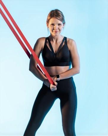 entrainement musculaire d'une jeune femme avec une bande de résistance élastique