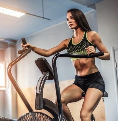 une sportive en train de s'entrainer avec un air bike pour améliorer son endurance cardio vasculaire