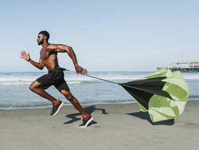 un homme utilisant un parachute de vitesse sur la plage : un matériel pour une préparation physique ciblant l'explosivité