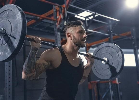 un homme appliquant la technique du rest pause sur un back squat