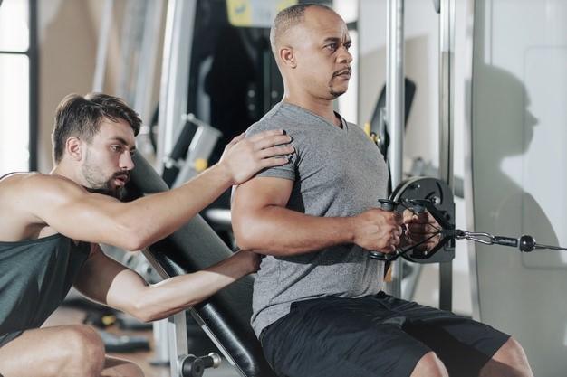 coach sportif corrigeant son élève sur un exercice de musculation