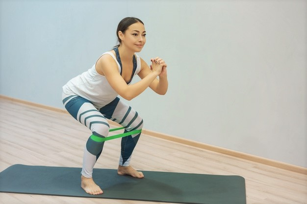 femme réalisant l'exercice du squat avec miniband