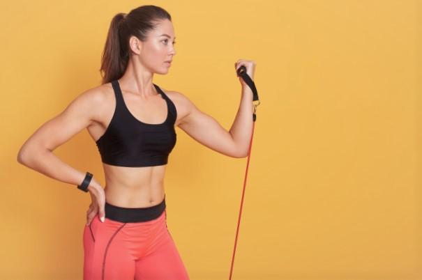 femme faisant du curl biceps avec un Elastique à poignées