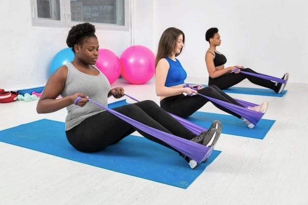 jeunes femmes faisant du fitness à domicile avec du matériel