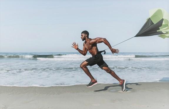 homme courant avec un parachute de vitesse sur la plage