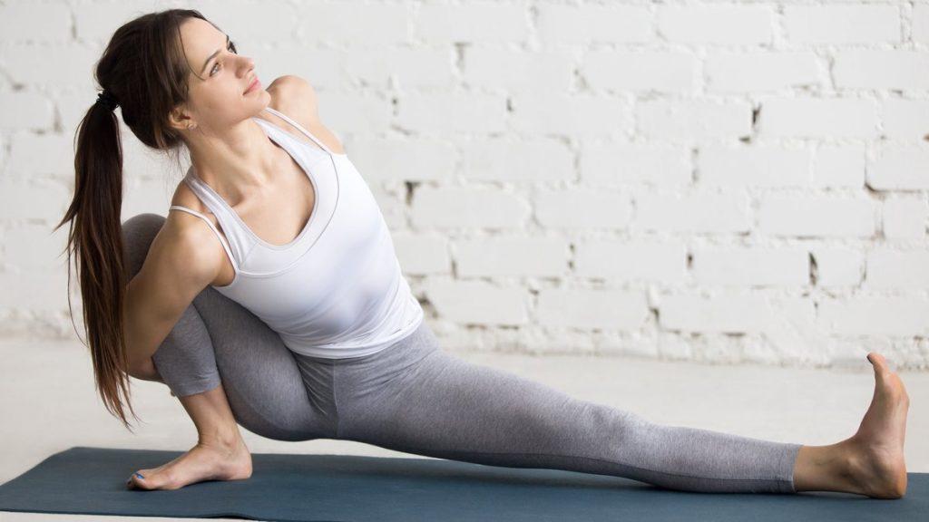 Une femme fait des exercices de gymnastique à son domicile