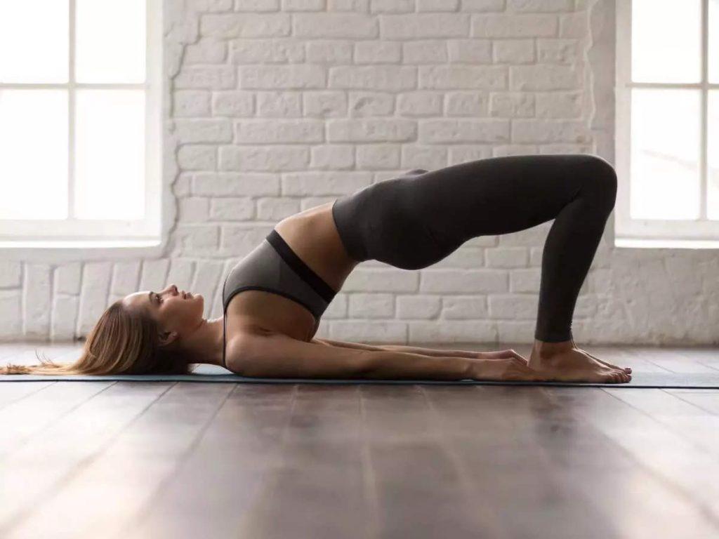 Une femme réalise un programme de gymnastique à son domicile