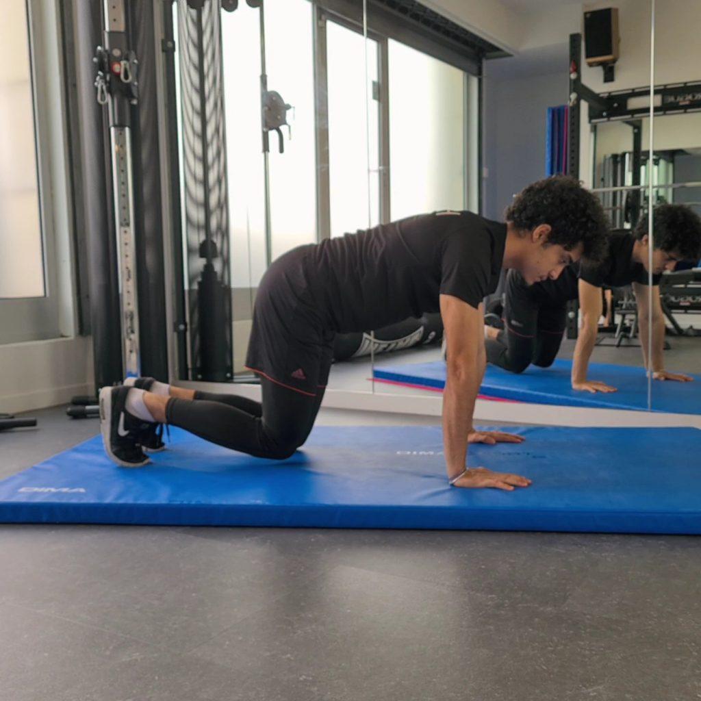 En posture de Bear Plank sur un tapis, un homme se prépare à réaliser cet exercice.
